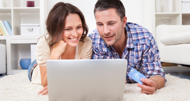 Couple Shopping Online Using Laptop And Credit Card